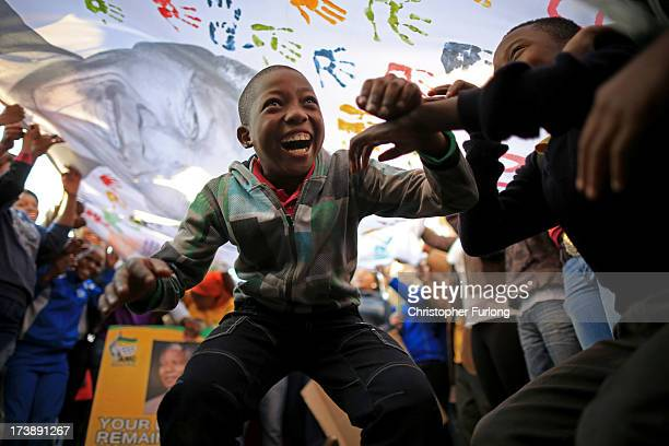 Children dance and celebrate as people wave a banner of Nelson Mandela to celebrate his 95th birthday outside the Mediclinic Heart Hospital where he...