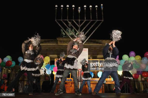 Children dance in front of a giant gaslit menorah shortly before members of the local Jewish community lit it in front of the Brandenburg Gate on the...