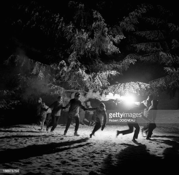 Children dance in the snow, 1958 in Laffrey, France.