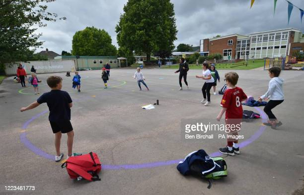Children dance on a measured and painted socially distanced circle in the playground as they wait to be picked up by their parents at Llanishen Fach...