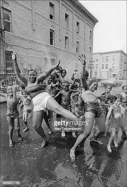 Children dance under the spray from a fire hydrant sprinkler in Brooklyn's Bushwick neighborhood New York New York July 20 1977