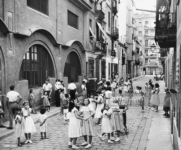 Children dancing in a street in Barcelona to the music of an organ grinder circa 1955