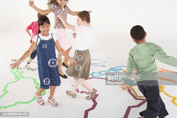 Children (6-9) dancing on outline map of earth