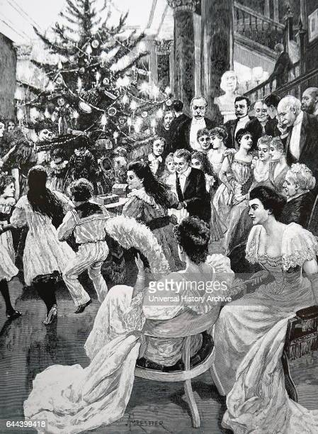 Children dancing round a Christmas tree laden with presents and decorated with candles England 1892
