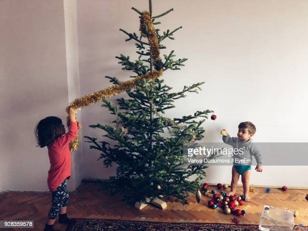 Children Decorating Christmas Tree At Home