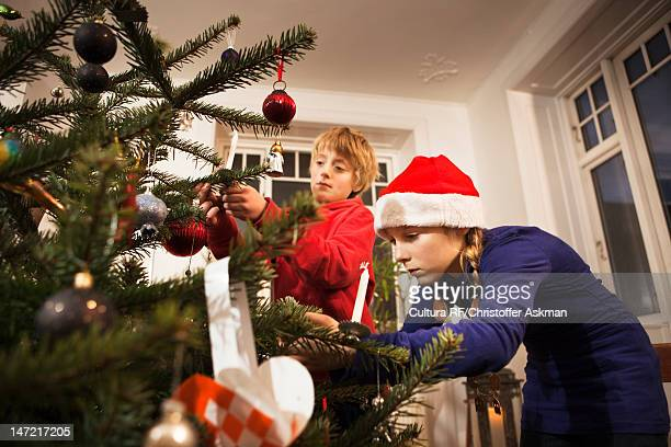 children decorating christmas tree - tradition stock pictures, royalty-free photos & images