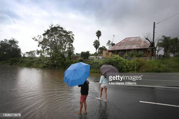 Children dip their feet in the rising floodwaters along the Hawkesbury River in the township of Windsor on March 22, 2021 in Sydney, Australia....