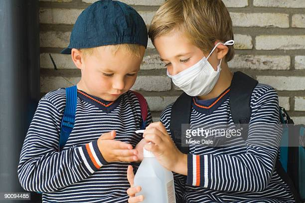 children disinfecting there hands against the flu - flu mask stock photos and pictures