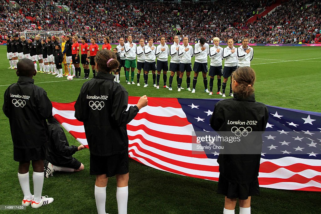 Children display the flag of the United States of America in the foreground with while the team sings the national anthem of during the Women's Football Semi Final match between Canada and USA, on Day 10 of the London 2012 Olympic Games at Old Trafford on August 6, 2012 in Manchester, England.
