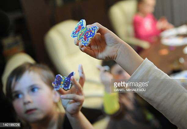 Children display their painted butterflies during martisor workshop organized by a company for the children of employees in Bucharest on February 22...