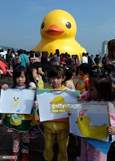Children display their paintings as visitors look at an 18metretall bath toy duck replica created by Dutch artist Florentijn Hofman as it floats its...