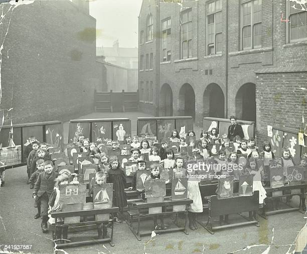 Children displaying their drawings Flint Street School Southwark London1908 Children standing at their desks in the playground proudly holding up...