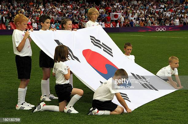 Children displays the national flag of Korea during the prematch ceremony during the Men's Football Bronze medal playoff match between Korea and...