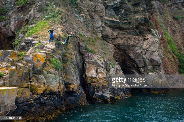 Children Diving In Sea From Cliff