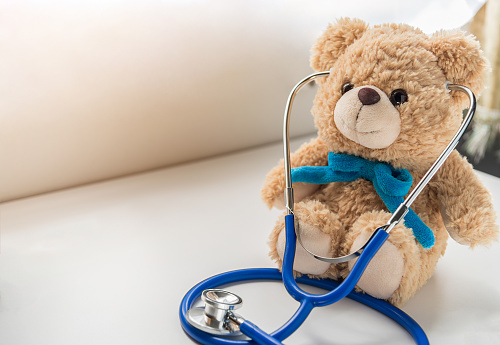 Children doctor concept - Teddy Bear with stethoscope. copy space 843098380