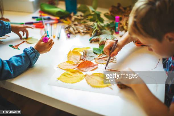 children doing autumn handcrafts - arti e mestieri foto e immagini stock