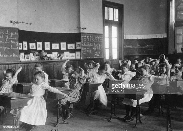 Children doing calisthenics while sitting at their desks in a classroom 5th Division public schools Washington DC