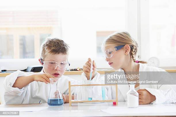 Children doing experiment with test tubes and flask