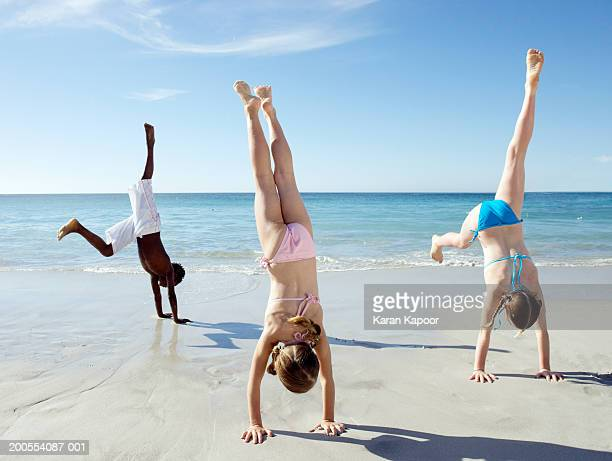 children ( 6-11) doing handstands on beach - girl with legs spread stock photos and pictures