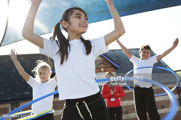 children doing pe in school with hoops - physical education stock pictures, royalty-free photos & images