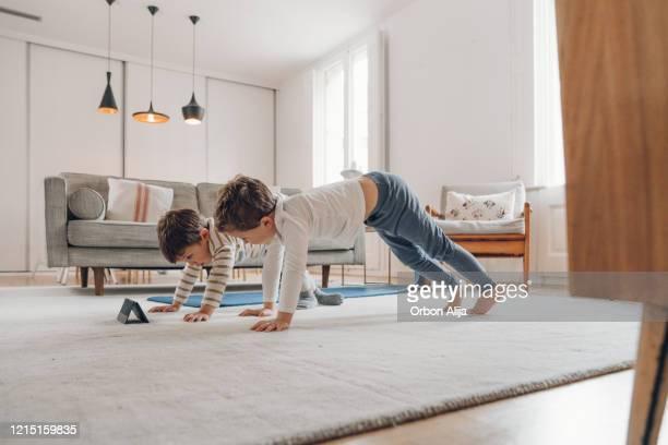 kinder, die zu hause yoga machen - turner syndrome stock-fotos und bilder