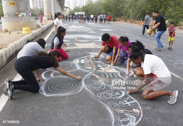 Children draw illustration on roadside during Raahgiri Day at Sector 55 Golf Course Road an event organised by MCG on June 17 2018 in Gurugram India...
