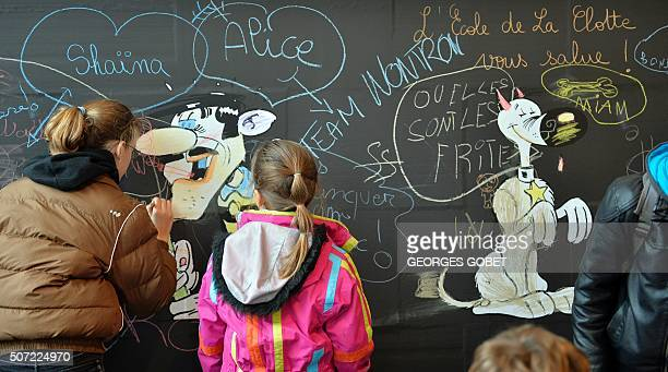 Children draw on a giant board as they visit an exhibition dedicated to the work of comic book artist Morris on January 28 2016 in Angouleme as part...