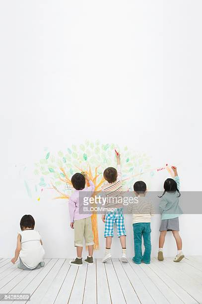 Children drawing a tree with markers