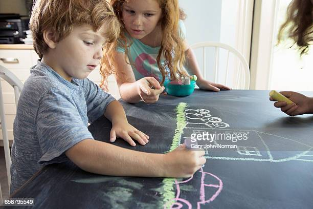 Children drawing happy scene on chalkboard