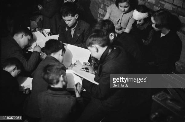 Children drawing in an art class given by London County Council teachers at an air raid shelter in Bermondsey London during the Blitz March 1941...