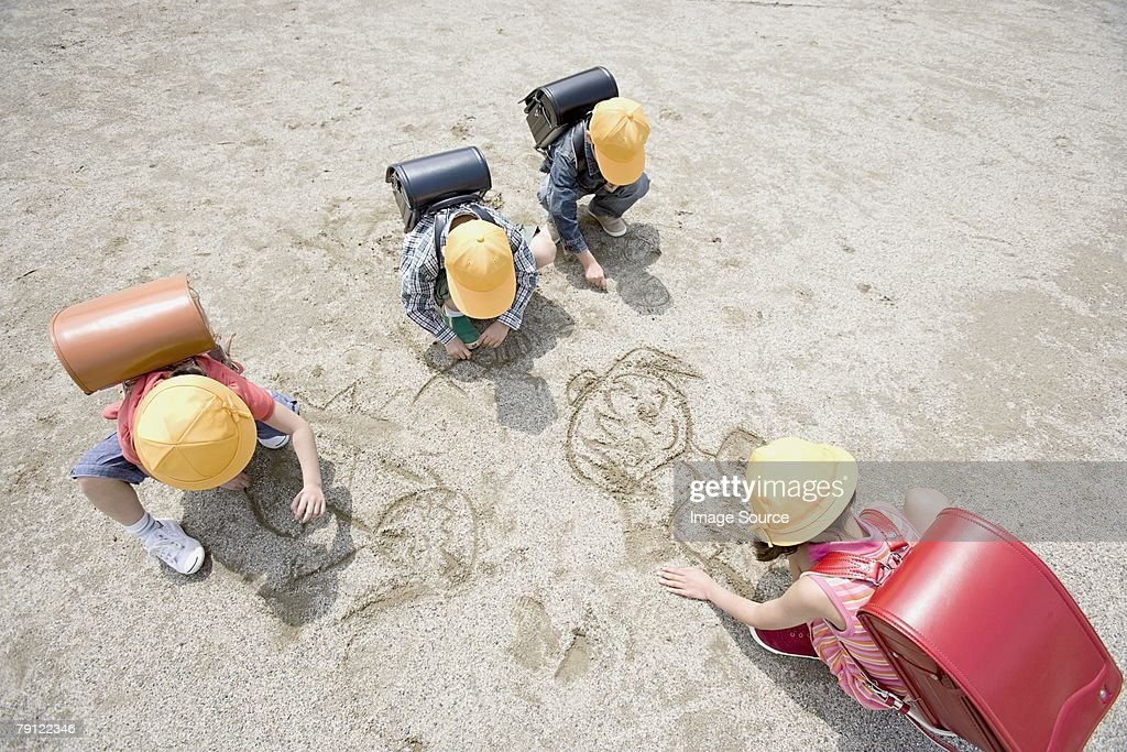 Children drawing in the sand : Stock Photo