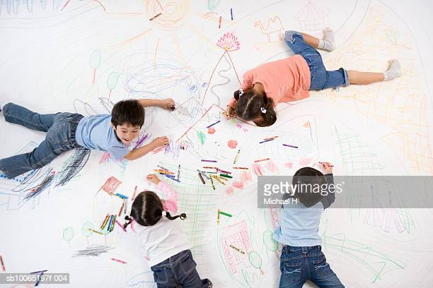Children (4-5 years) drawing on floor with crayons, overhead view