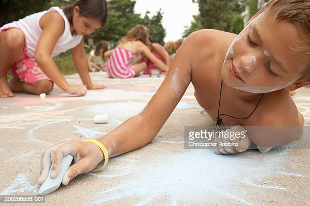Children (6-12) drawing on ground with chalk (focus on boy)