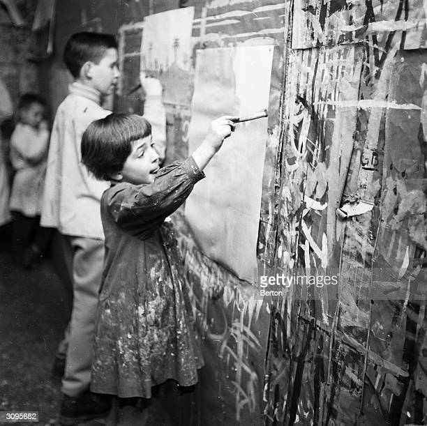 Children drawing pictures on a paintsplattered wall in France