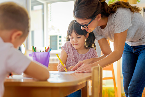 Children drawing with smiling preschool teacher assisting them 1054793552