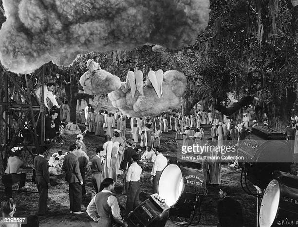 Children dressed as angels sitting on a fake cloud suspended from a studio ceiling as a film crew prepare to shoot a scene for the film 'Green...