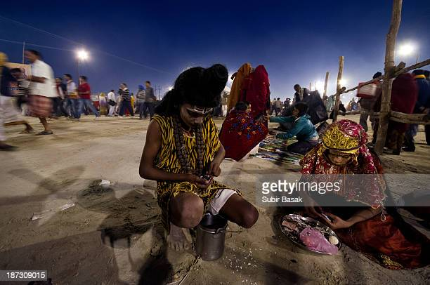 Children dressed as Hindu gods counting alms on the end of a auspicious bathing day during the Maha Kumbh Mela on February 15, 2013 in Allahabad,...
