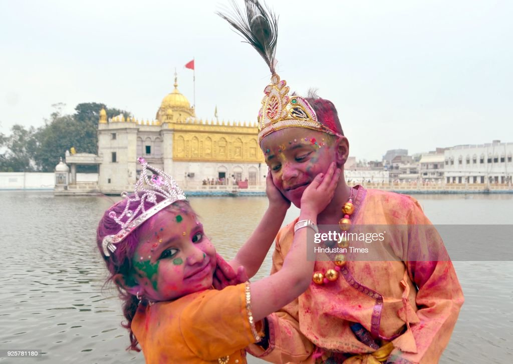 Children dressed as Lord Krishna and Radha play with coloured powder as celebrating Holi festival at Durgiana Temple on March 1 2018 in Amritsar...