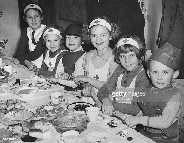 Children dressed as nurses and military men prepare to pull apart their party crackers before a dessertladen table in an air raid shelter on October...