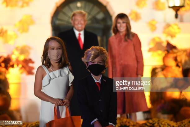 Children dressed as the Presidential couple pose in front of US President Donald Trump and First Lady Melania Trump at a Halloween celebration at the...
