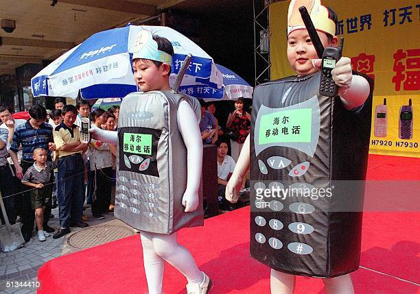 Children dressed in costumes to look like mobile phones parade at a mall in Beijing 19 June 2000 The number of operational mobile phones reached 60...