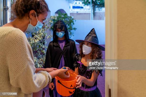 children dressed in halloween costumes trick-or-treating in covid-19 times - trick or treat stock pictures, royalty-free photos & images