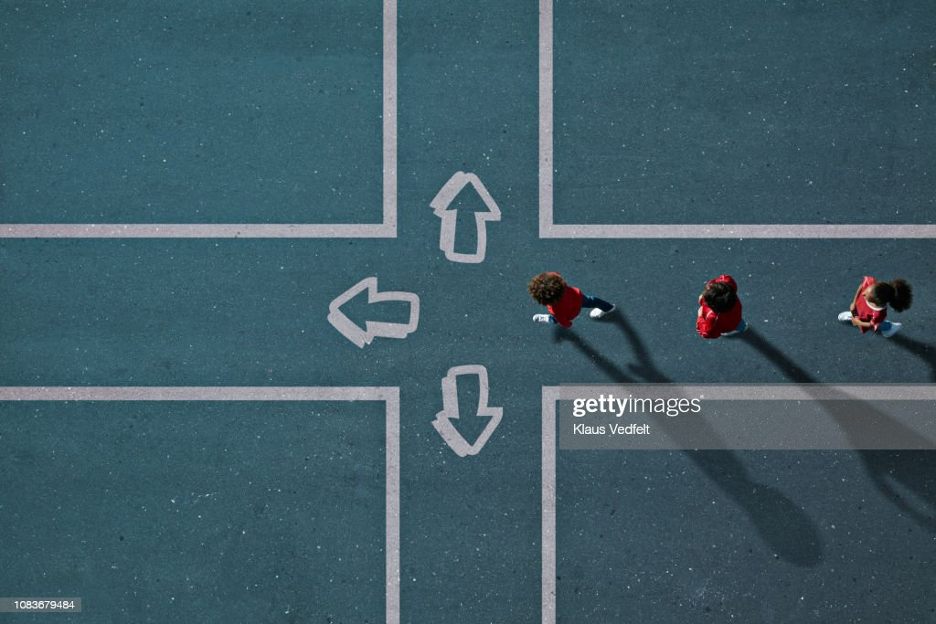 Children dressed in red approaching painted crossroad with arrows : Stockfoto