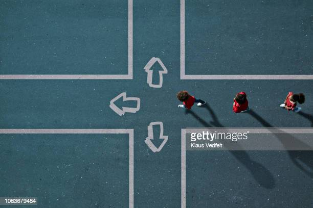 children dressed in red approaching painted crossroad with arrows - three people stock pictures, royalty-free photos & images