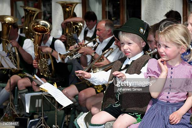 Children dressed in traditional Bavarian costume watch the erection of a 28 metres long maypole on May 1 in Elbach near Miesbach Germany The maypole...