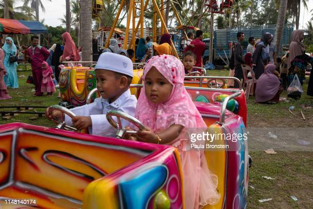 Children dressed in traditional clothing enjoy rides and games at the Talo Kapo beach as Muslims celebrate Eid alFitr on June 5 2019 in Pattani...