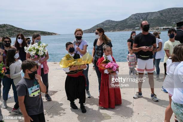 Children dressed in traditional Greek clothing join local residents on the Greek island of Leipsoi as they greet members of the Aegean Team, an NGO...