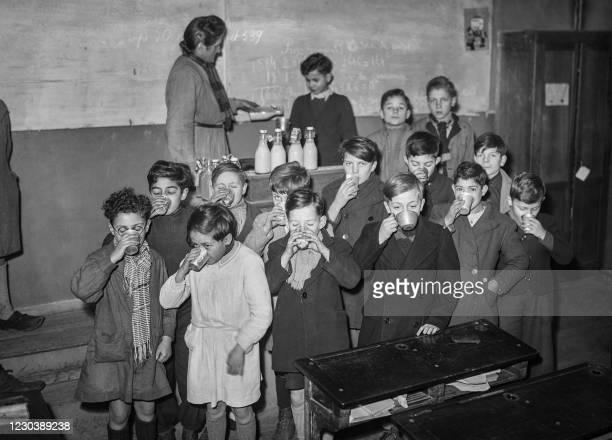 Children drink a glass of milk, in a classroom, in December 1944 in Paris.