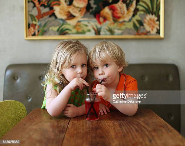 2 children drinking in the same glass with a straw - 分かち合い ストックフォトと画像
