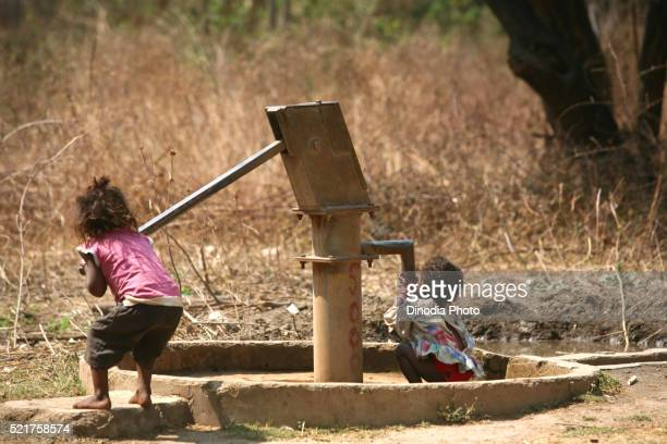 Children drinking water from hand pump in Jharkhand, India